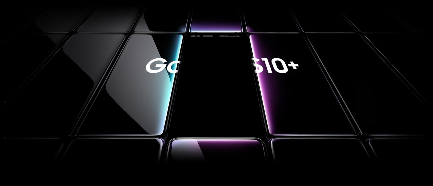 Several Galaxy S10 plus phones all laid flat and seen at an angle. All are black except the one in the middle, which is shown with a prismatic gradient onscreen with Galaxy S10 plus overlaid on top of it and the two phones on either side.