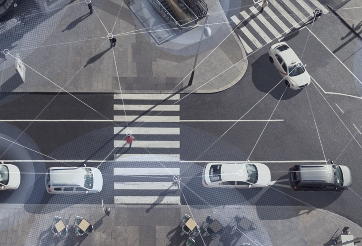 Aerial shot of a street scene with cars driving and people walking, with lines overlaid on top to show the connectivity of Wi-Fi and LTE.